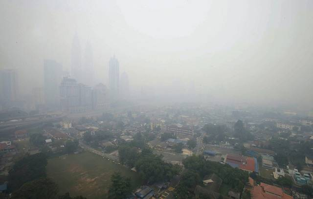 A combination picture shows Malaysia's capital of Kuala Lumpur covered with haze (top) at 1230 p.m. (0430 GMT) on June 23, 2013 with the pollution standards index (PSI) at 111, and five days ago at 1200 pm (0400 GMT) on June 18 with the PSI at 72. Malaysia declared a state of emergency in two parts of the southern state of Johor on Sunday as smoke from land-clearing fires in Indonesia pushed air pollution above the level considered hazardous. A PSI reading above 300 indicates that air pollution is hazardous. REUTERS/Bazuki Muhammad (MALAYSIA - Tags: ENVIRONMENT HEALTH SOCIETY TPX IMAGES OF THE DAY)