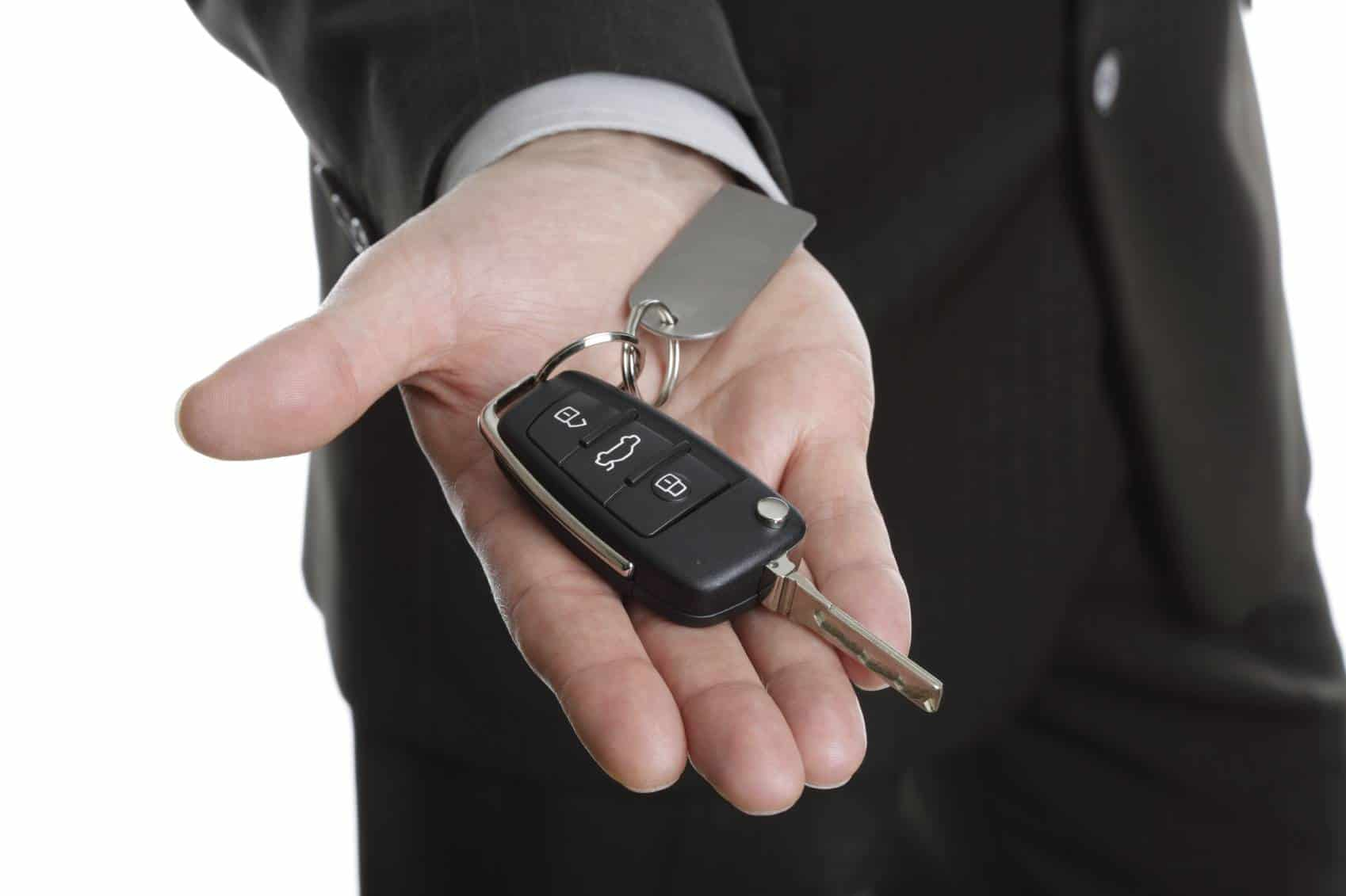 Car salesman or rental man giving over a car key