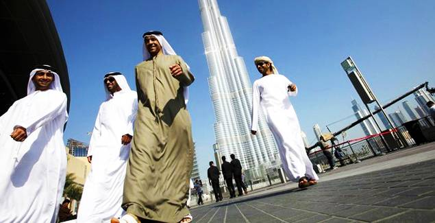A group of Emiratis walk past the Burj Dubai Tower, the tallest tower in the world, on the day of its inauguration, in Dubai January 4, 2010.  Started at the height of the economic boom and built by some 12,000 labourers, the world's tallest building will open today in Dubai as the glitzy emirate seeks to rekindle optimism after its financial crisis.  REUTERS/Ahmed Jadallah (UNITED ARAB EMIRATES - Tags: CITYSCAPE BUSINESS CONSTRUCTION SOCIETY)