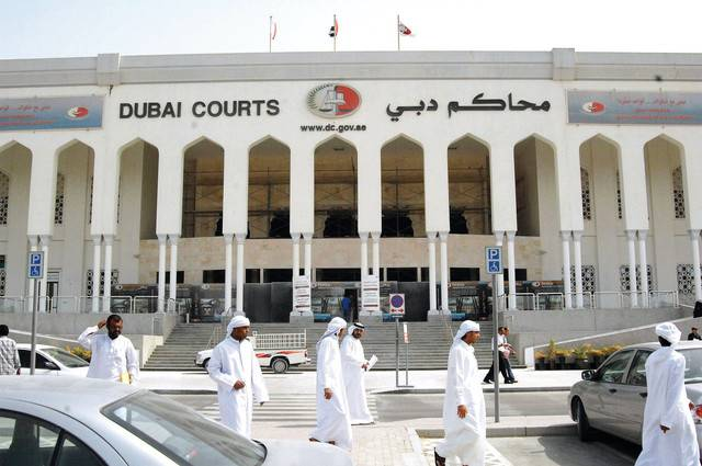 People are seen walking outside the Dubai Courts, where a British couple accused of public indecency, are to be tried in Dubai, United Arab Emirates, Tuesday, Sept. 9, 2008. A court official said Tuesday that the hearings in the trial of a British couple accused of having sex on a Dubai beach have been postponed for another month. (AP Photo/Aziz Shah)