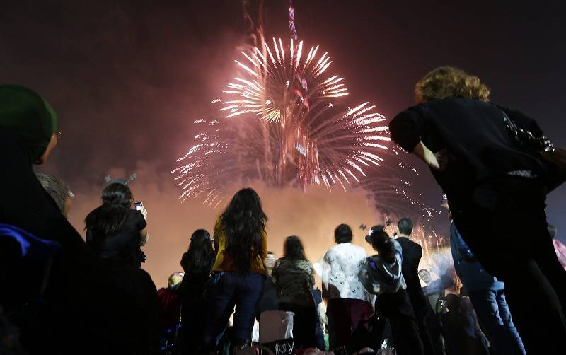 People look at a firework display during a New Year celebration on January 1, 2015 in Dubai.  AFP PHOTO / KARIM SAHIB