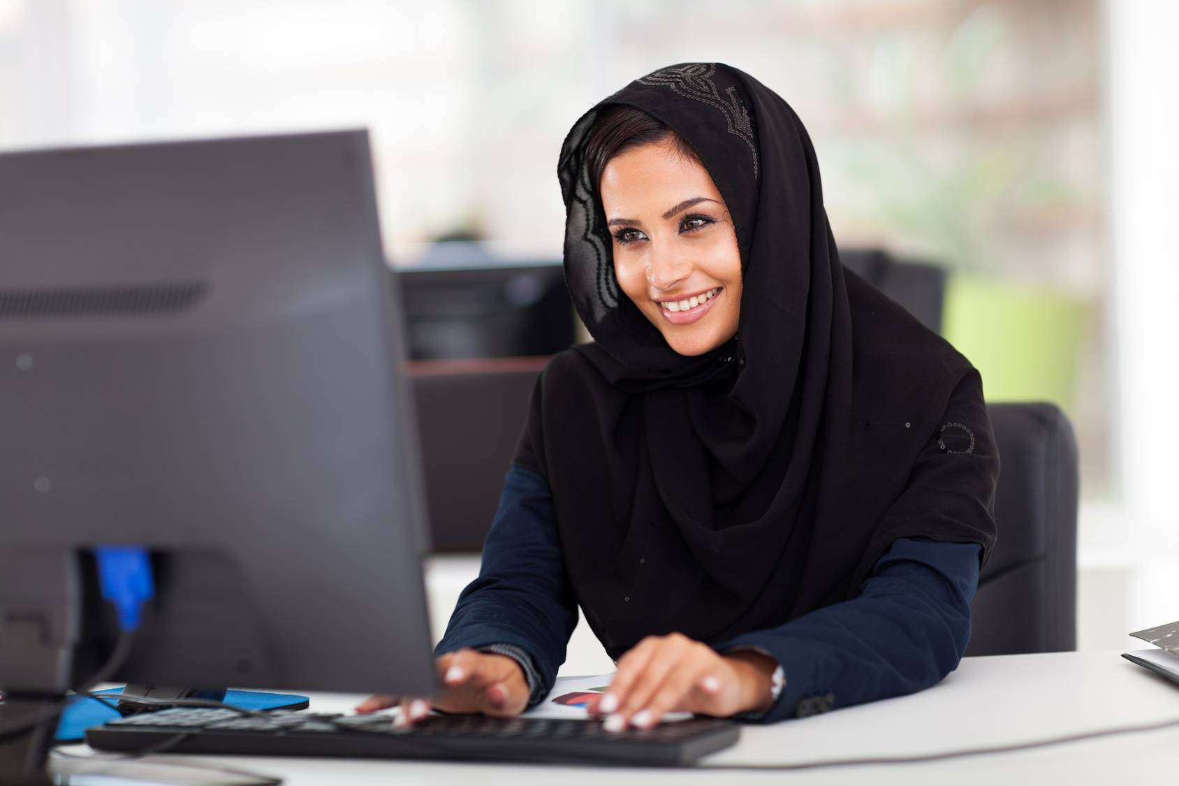 attractive female Arabic corporate worker working on computer