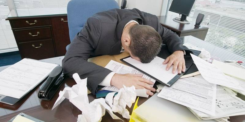 Businessman face-down on messy desk