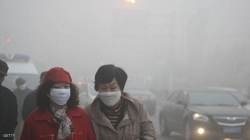 HARBIN, CHINA - OCTOBER 22:  (CHINA OUT) Pedestrians wearing masks walk along a road as heavy smog engulfs the city on October 22, 2013 in Harbin, China. Expressways, schools and an airport remain closed as heavy smog continues to disrupt northeast China.  (Photo by ChinaFotoPress/Getty Images)