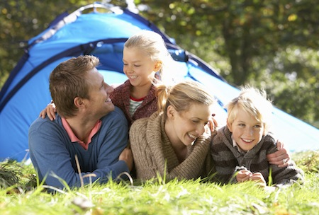 Young family laying outside tent