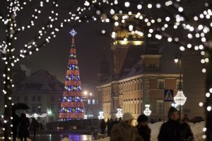 People walk at night in front of a lit Christmas tree near Royal Castle at Old Town in Warsaw, December 22, 2010. REUTERS/Kacper Pempel (POLAND - Tags: CITYSCAPE ENVIRONMENT IMAGES OF THE DAY)